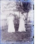 Two women posing by tree