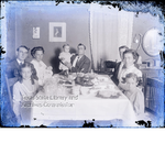 Group portrait of family around dinner table