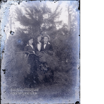 Three women posing by tree