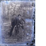Two men sitting on a stump