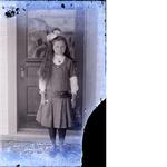 Young girl standing in front of door