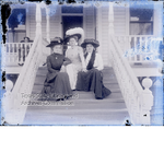 Three women sitting on front steps of house with porch