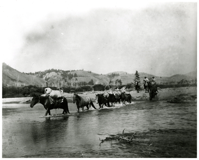 Three Riders And Train Of Pack Horses Crossing A River