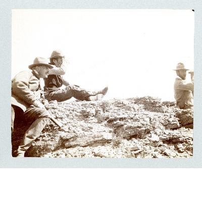 Three men; one with binoculars, one with firearm sitting, one looking from a ridge