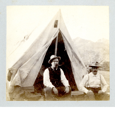 Two men posed seated in front of a tent