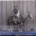 Man on horseback with young child