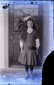 Young girl standing in front of door