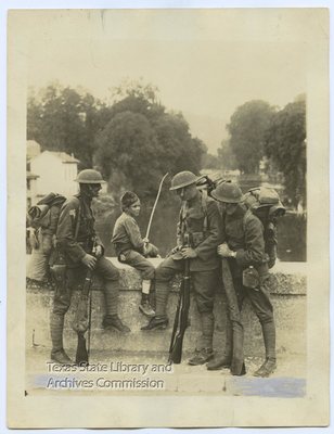 Signal Corps Photo. Boy fishing from bridge with troops, Bayell, France